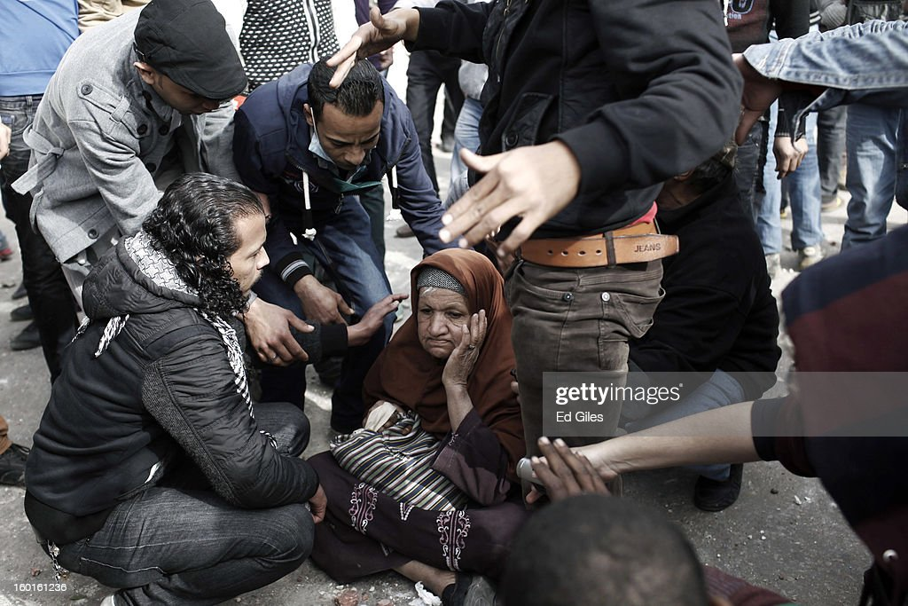 Egyptian protesters try to convince an elderly woman to move out of the way after sitting down in between opposing sides during a demonstration in Tahrir Square on January 27, 2013 in Cairo, Egypt. Violent protests continued across Egypt two days after the second anniversary of the Egyptian Revolution that overthrew former President Hosni Mubarak on January 25, and one day after the announcement of the death penalty for 21 suspects in connection with a football stadium massacre one year before. The verdict was announced in a case over the deaths of more than seventy fans of Egypt's Al-Ahly football club in a stadium massacre on February 1, 2012, in the northern city of Port Said, during a brawl that began minutes after the final whistle of a match between Al-Ahly and opposing side, Al-Masry. 21 fans of the opposing side, Al-Masry, were given the death penalty, a verdict that must now be approved by Egypt's Grand Mufti. (Photo by Ed Giles/Getty Images).