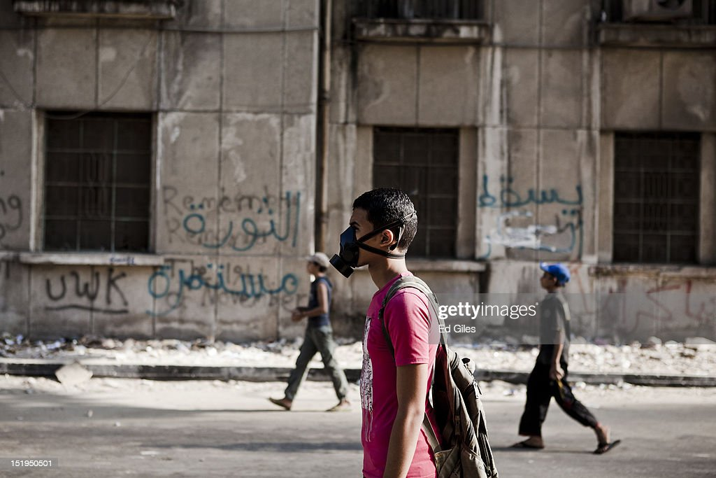 Egyptian protesters walk towad police lines during clashes near the United States Embassy and Cairo's Tahrir Square on September 13, 2012 in Cairo, Egypt. At least 13 people have been injured, including 10 riot police, in clashes between protesters and security forces overnight. Protests have continued for a third day in central Cairo, with Egyptians demonstrating against a US-made film said to be defaming the Prophet Mohammed, whose trailer had recently been released on Youtube and translated into Arabic. Demonstrations turned violent late Wednesday night near the US Embassy, after Egyptians demonstrated at the Embassy compound and breached its perimeter walls on Tuesday. Christopher Stevens, a State Department officer at the consulate in the Libyan city of Benghazi, died in an a later attack along with three other embassy staff after violence erupted over the film.