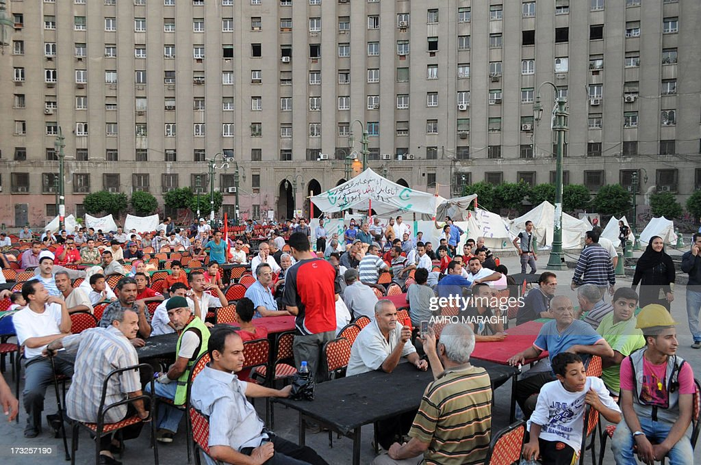 Egyptian protesters who gather in Tahrir square sit down at tables before being given Ramadan meal boxes on July 10, 2013 in front of the al-Mogamma administrative building in the Egyptian capital Cairo. AFP PHOTO AMRO MARAGHI