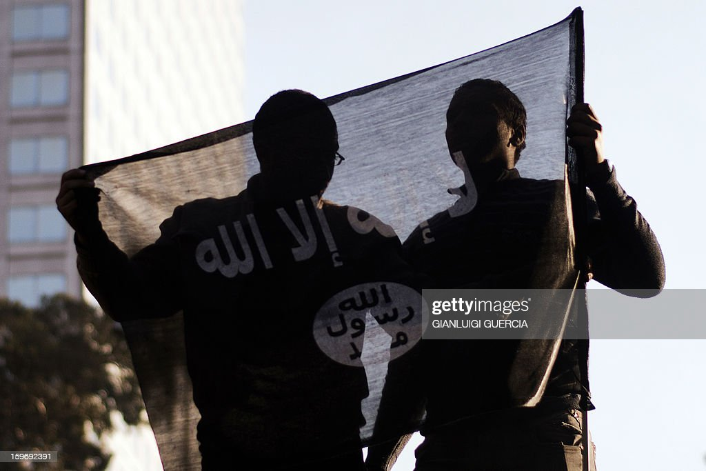 Egyptian protestors are seen through an Islamist flag during a demonstration organised by Egyptian Islamists against the French intervention in Mali on January 18, 2013 in Cairo. The brother of Al-Qaeda chief Ayman al-Zawahiri joined dozens of Egyptian Islamists in a protest near the French embassy in Cairo. AFP PHOTO/GIANLUIGI GUERCIA