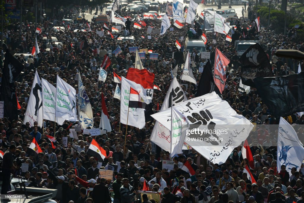 Egyptian protestors waving their national flag alongside other banners march from Mostafa Mahmoud Mosque to Tahrir Square on January 25, 2013, during a demonstration to demand change, two years after the uprising that ousted Hosni Mubarak and ushered in an Islamist government, as sporadic clashes erupted nearby.