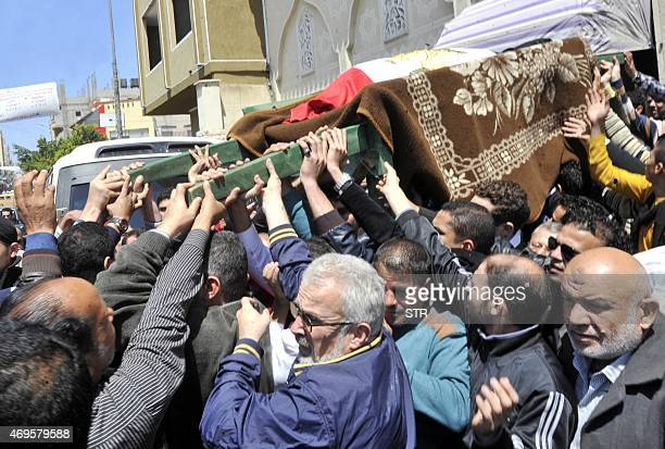 Egyptian relatives and mourners carry the body of police officer Amr Shoukry during his funeral in north Sinai's provincial capital of AlArish on...