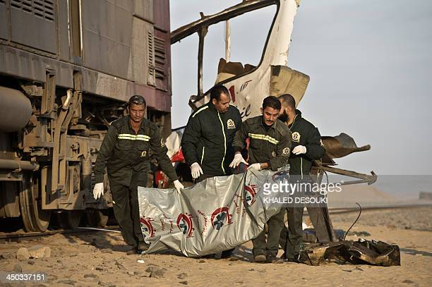 Egyptian rescuers wrap the body of a victim on the site of an accident near a railway crossing where a train ploughed into a truck and a minibus on...