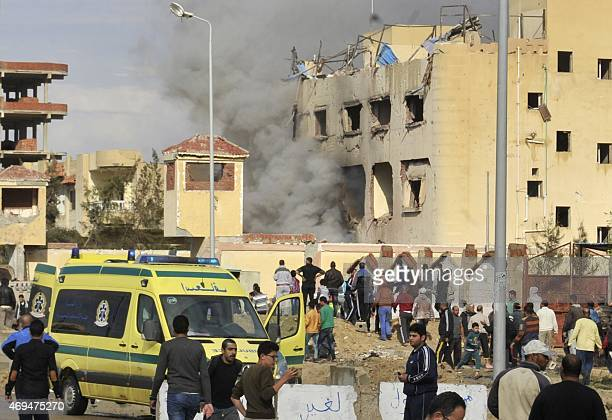 Egyptian residents and emergency personnel gather at the site of a car bomb explosion that targeted a police station in North Sinai's provincial...