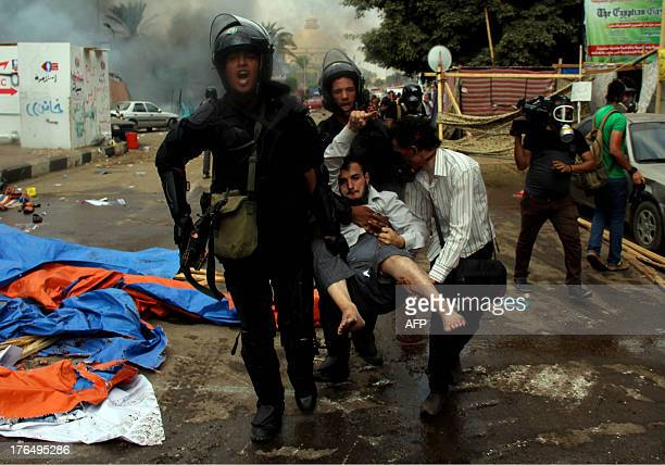 Egyptian riot police carry a wounded demonstrator during clashes as security forces try to disperse protest camps on August 14 2013 that were set up...