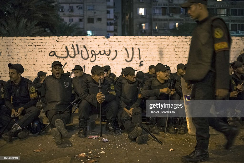 Egyptian riot police rest as others stand guard in front of Dokki police station on December 16, 2012 in Cairo, Egypt. Egyptian police were on high alert after news of a planned protest by Salafist supporters of Hazem Abu Ismail, after an attack on WAFD party headquarters last night on election day. The protest was cancelled after an announcement on Hazem Abu Ismail's Facebook account.