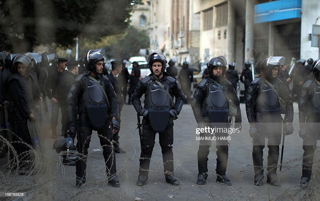 Egyptian riot police stand guard outside the Shura Council, the upper house of parliament where the Constituent Assembly drafted the country's new constitution, as protesters against Egypt's President Mohamed Morsi chant slogans in front of them, while Morsi gives a speech before a newly empowered senate in Cairo on December 29, 2012. Morsi said in the address, a disputed new constitution guaranteed equality for all Egyptians, and downplayed the country's economic woes.