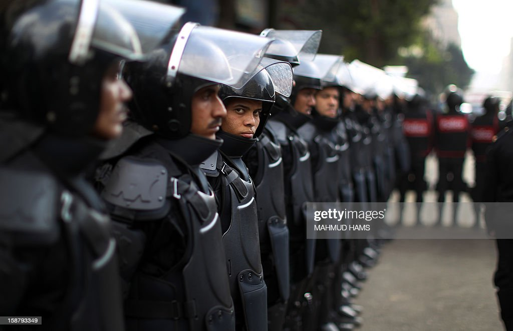 Egyptian riot police stand guard outside the Shura Council, the upper house of parliament where the Constituent Assembly drafted the country's new constitution, as protesters against Egypt's President Mohamed Morsi demonstrate, while Morsi gives a speech before a newly empowered senate in Cairo on December 29, 2012. Morsi said in the address, a disputed new constitution guaranteed equality for all Egyptians, and downplayed the country's economic woes. AFP PHOTO/MAHMUD HAMS