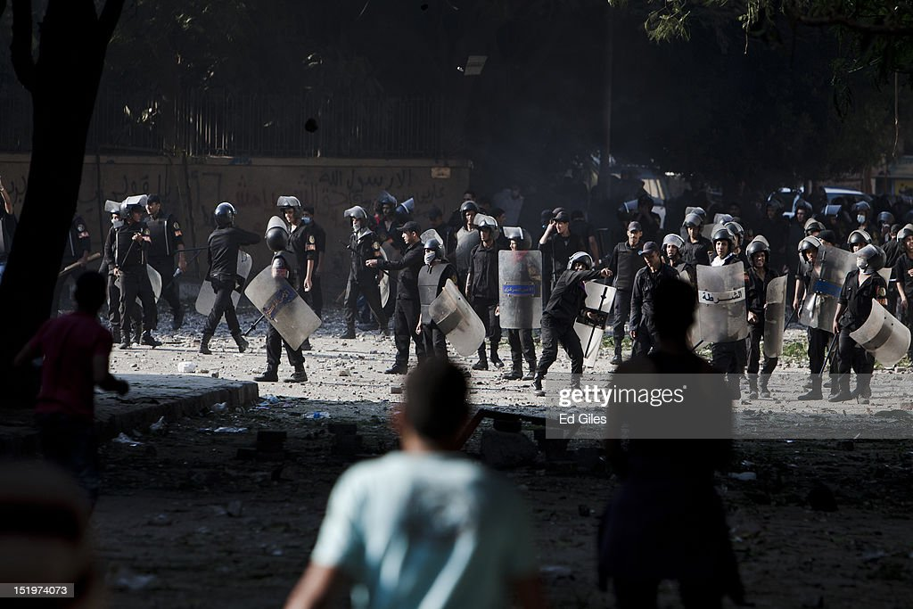 Egyptian riot police throw rocks toward protesters during clashes near the United States Embassy and Tahrir Square on September 14, 2012 in Cairo, Egypt. Over two hundred people have been injured in clashes between protesters and security forces. Protests have continued into a fourth day in central Cairo, with Egyptians demonstrating against a US-made film said to be defaming the Prophet Mohammed, whose trailer had recently been released on Youtube and translated into Arabic. Egyptian authorities began construction of a concrete barrier early Friday morning to stop demonstrations planned across the country for Friday from reaching the US Embassy, after Egyptians demonstrated at the Embassy compound and breached its perimeter walls on Tuesday.
