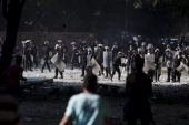 Egyptian riot police throw rocks toward protesters during clashes near the United States Embassy and Tahrir Square on September 14 2012 in Cairo...