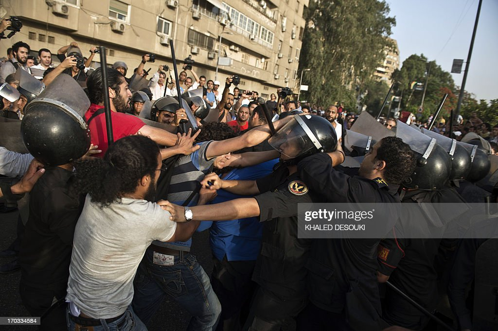Egyptian riot police try to disperse clashes between supporters the ruling Muslim Brotherhood and protestors calling for the resignation of Culture Minister Alaa Abdel Aziz in Cairo on June 11, 2013. The sacking of Egypt's Opera House head has triggered a new political battle against President Mohamed Morsi, this time by artists who accuse the Islamist's Muslim Brotherhood of aiming to control cultural institutions. Aziz, appointed in a recent cabinet reshuffle, is considered close to the Brotherhood, although he is not a member. AFP PHOTO / KHALED DESOUKI