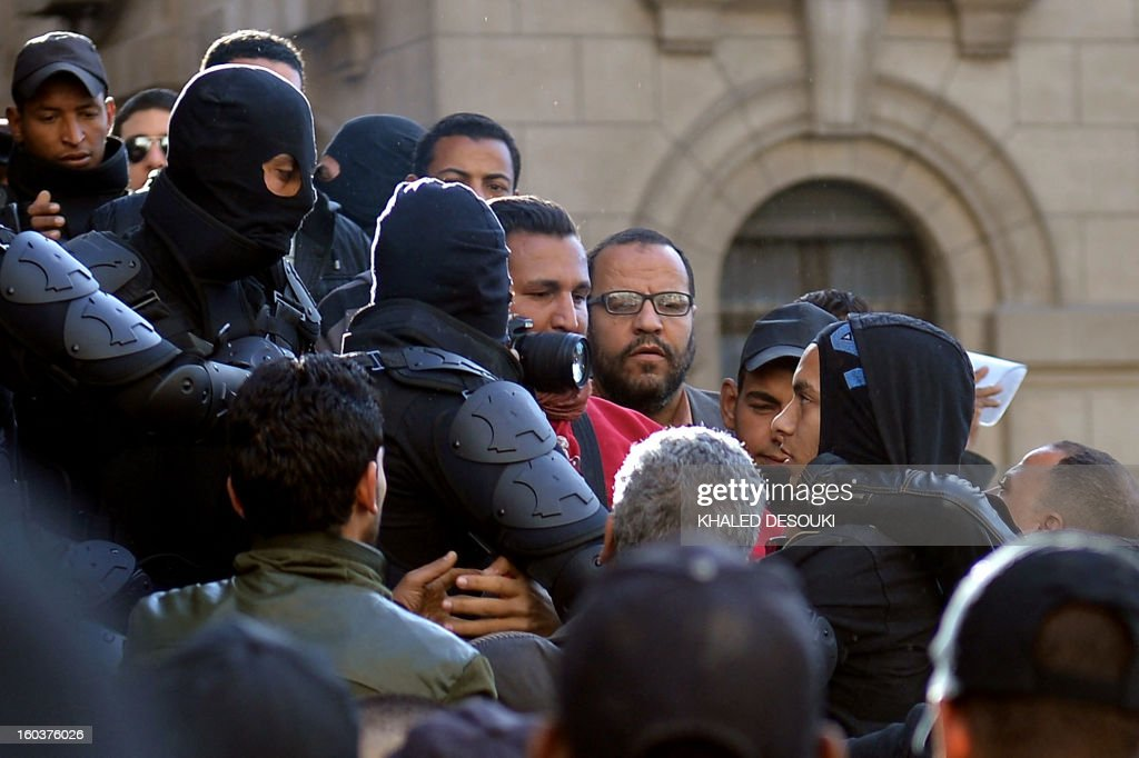 Egyptian riot policemen detain a youth (R) suspected of being a member of the 'Black Bloc' group during a demonstration outside the high court in central Cairo on January 30, 2013. Egyptian authorities detained suspected 'Black Bloc' members as they protested an order by the public prosecutor to arrest anyone from the shadowy opposition group, an AFP journalist said. Presenting themselves as the defenders of protesters opposed to President Mohamed Morsi's rule, the Black Bloc reportedly models itself on anarchist groups of the same name in Europe and the United States.