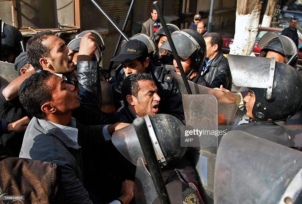 Egyptian riot policemen evacuate protestors, PhDs and masters, breaking up their sit-in in front of the home of Prime Minister Hisham Qandil to ask for jobs in Cairo on January 21, 2013. Police arrested twelve of them, imposed a security perimeter around Qandil's home and surrounded the protesters to break up the sit-in.