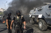 Egyptian riot policemen secure a street near an armoured vehicle during a rally of supporters of the Muslim Brotherhood movement to mark the first...