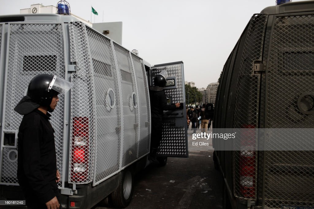 Egyptian riot policemen stand by an armoured vehicle during a demonstration in Tahrir Square on January 27, 2013 in Cairo, Egypt. Violent protests continued across Egypt two days after the second anniversary of the Egyptian Revolution that overthrew former President Hosni Mubarak on January 25, and one day after the announcement of the death penalty for 21 suspects in connection with a football stadium massacre one year before. The verdict was announced in a case over the deaths of more than seventy fans of Egypt's Al-Ahly football club in a stadium massacre on February 1, 2012, in the northern city of Port Said, during a brawl that began minutes after the final whistle of a match between Al-Ahly and opposing side, Al-Masry. 21 fans of the opposing side, Al-Masry, were given the death penalty, a verdict that must now be approved by Egypt's Grand Mufti. (Photo by Ed Giles/Getty Images).