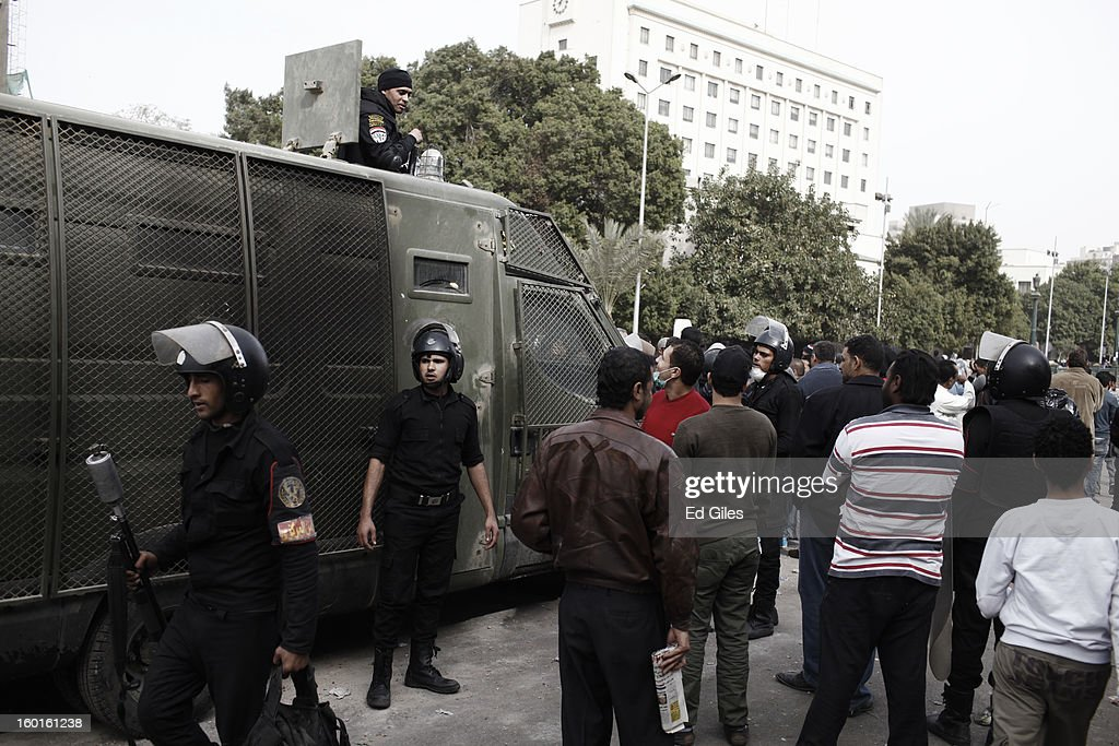 Egyptian riot policemen stand by an armoured vehicle parked amonst Egyptian civilians during a demonstration in Tahrir Square on January 27, 2013 in Cairo, Egypt. Violent protests continued across Egypt two days after the second anniversary of the Egyptian Revolution that overthrew former President Hosni Mubarak on January 25, and one day after the announcement of the death penalty for 21 suspects in connection with a football stadium massacre one year before. The verdict was announced in a case over the deaths of more than seventy fans of Egypt's Al-Ahly football club in a stadium massacre on February 1, 2012, in the northern city of Port Said, during a brawl that began minutes after the final whistle of a match between Al-Ahly and opposing side, Al-Masry. 21 fans of the opposing side, Al-Masry, were given the death penalty, a verdict that must now be approved by Egypt's Grand Mufti. (Photo by Ed Giles/Getty Images).