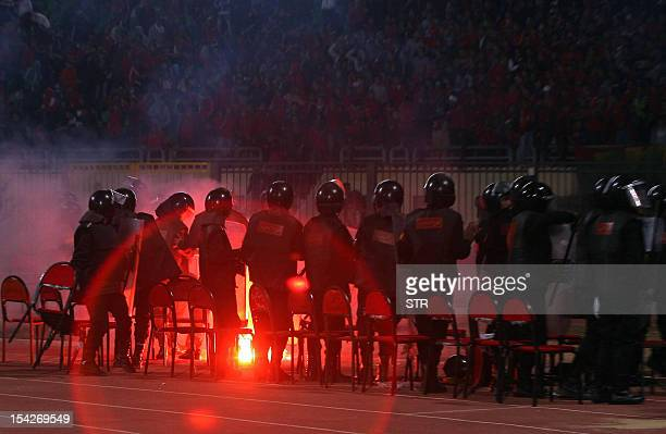 Egyptian riot policemen stand guard as a flare is thrown during a football match between AlMasry and AlAhly in Port Said on February 1 2012 At least...
