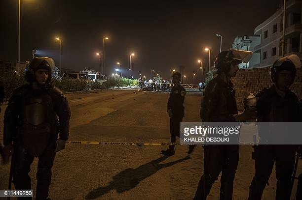 Egyptian riot policemen stand guard as officials inspect the wreckage of a car bomb that exploded in a Cairo suburb after Egypt's deputy prosecutor...