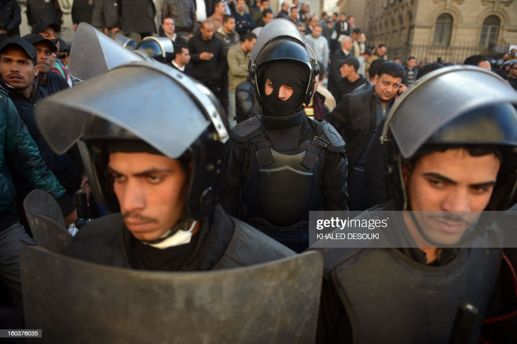 Egyptian riot policemen stand guard during a demonstration outside the high court in central Cairo on January 30, 2013. Egyptian authorities detained suspected 'Black Bloc' members as they protested an order by the public prosecutor to arrest anyone from the shadowy opposition group, an AFP journalist said. Presenting themselves as the defenders of protesters opposed to President Mohamed Morsi's rule, the Black Bloc reportedly models itself on anarchist groups of the same name in Europe and the United States. AFP PHOTO / KHALED DESOUKI
