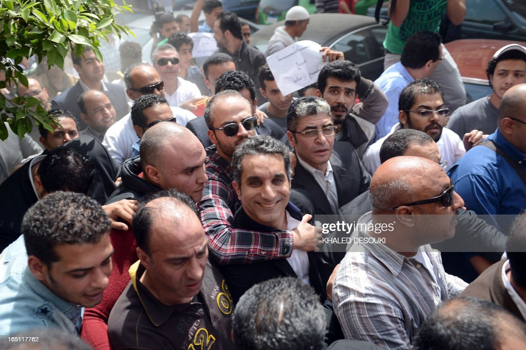 Egyptian satirist and television host Bassem Youssef (C) is surrounded by his supporters upon his arrival at the public prosecutor's office in the high court in Cairo, on March 31, 2013. Egypt's public prosecutor ordered the arrest of popular satirist Youssef over alleged insults to Islam and to President Mohamed Morsi, in the latest clampdown on critical media.