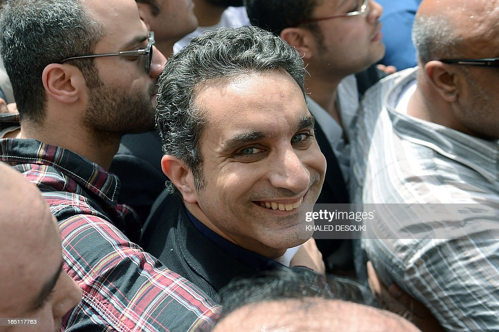 Egyptian satirist and television host Bassem Youssef is surrounded by his supporters upon his arrival at the public prosecutor's office in the high court in Cairo, on March 31, 2013. Egypt's public prosecutor ordered the arrest of popular satirist Youssef over alleged insults to Islam and to President Mohamed Morsi, in the latest clampdown on critical media.