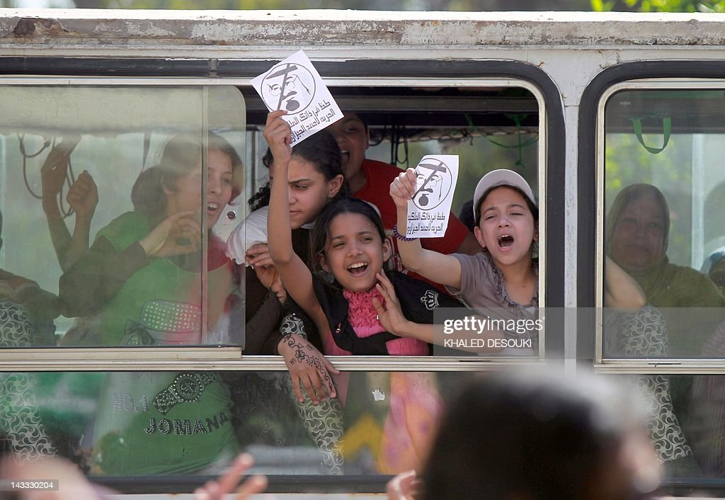 Egyptian school girls shout slogans as they drive past a demonstration in front of Saudi Arabian embassy in Cairo on April 24, 2012, calling for the release of Egyptians who have been detained in the kingdom, including Ahmed al-Gizawi (portrait) who arrested on April 17, upon his arrival to Saudi Arabia to perform the omra, a minor pilgrimage to Islam's holiest sites in Mecca and Medina. Egypt has asked Saudi Arabia to say why it arrested Gizawi who is an Egyptian rights lawyer and activist on arrival at Jeddah airport.