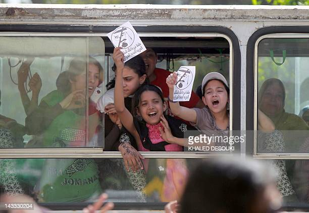 Egyptian school girls shout slogans as they drive past a demonstration in front of Saudi Arabian embassy in Cairo on April 24 calling for the release...
