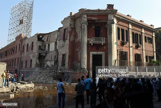Egyptian security and citizens look at the the destroyed facade of the Italian consulate building following a powerful bomb explosion killing one...