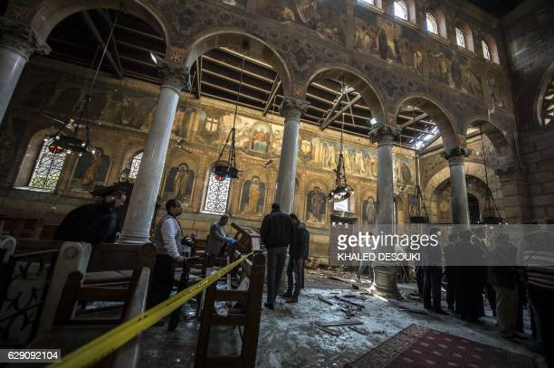 TOPSHOT Egyptian security forces and officials inspect the scene of a bomb explosion at the Saint Peter and Saint Paul Coptic Orthodox Church on...