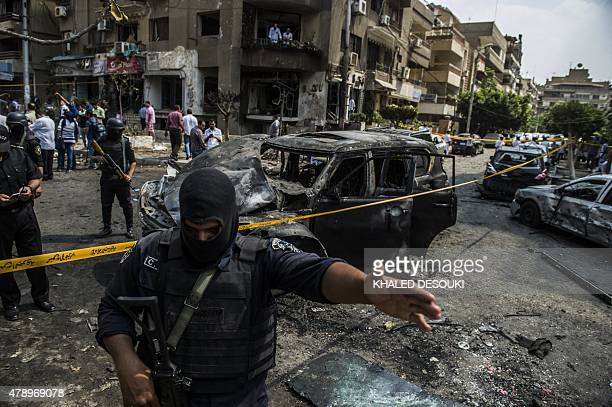 Egyptian security forces stand guard at the site of a bomb attack that targeted the convoy of Egyptian state prosecutor Hisham Barakat who died hours...