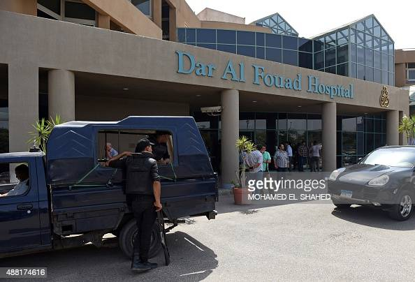 Egyptian security members stand guard as newly appointed Tourism Minister Khaled Ramy arrives at the Dar alFouad Hospital in a western Cairo suburb...