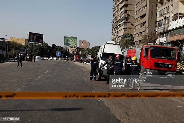 Egyptian security officers and firemen stand at the scene of a bomb attack that reportedly targeted an Egyptian police car parked by a metro station...