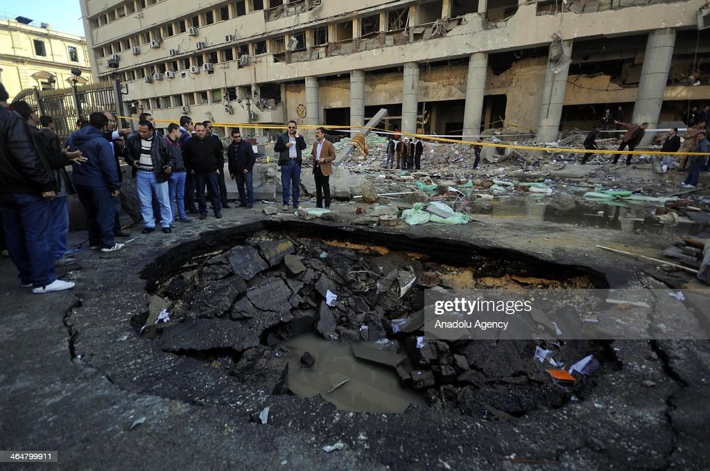 Egyptian security officers cordon off the site of a car bomb attack targeted Cairo security headquarters on January 24, 2014 in Egypt. At least five people were killed and many others wounded in a series of bombings on January 24, 2014 in Cairo, Egypt.