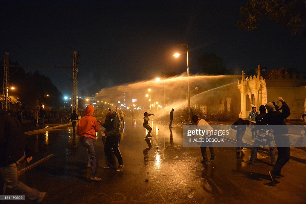 Egyptian security use water cannon as protesters throw stones into the grounds of the presidential palace in Cairo, on February 11, 2013, as the opposition held rallies to mark the second anniversary of former president Hosni Mubarak's overthrow.