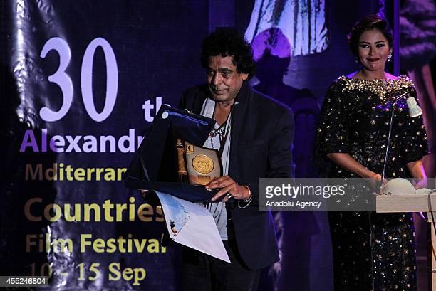Egyptian singer Mohamed Mounir poses with his award during the 30th Alexandria Film Festival in Alexandria Egypt on September 10 2014 The film...