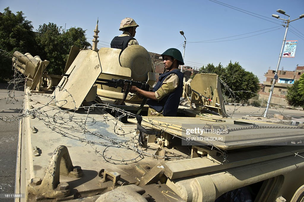 Egyptian soldiers hold a position on top of a tank on the road leading to the village of Kerdassah on the outskirts of Cairo, on September 19, 2013. A police general was killed when Egyptian security forces stormed Kerdassah in the latest crackdown on Islamist militants, security officials said.