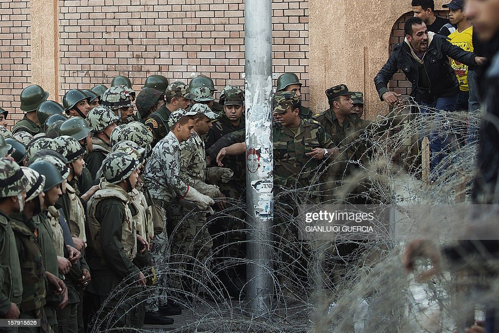 Egyptian soldiers prevent demonstrators from crossing over a barbed wire fence as thousands gather near the presidential palace in Cairo to protest against a draft constitution and President Mohamed Morsi's sweeping powers decree on December 7, 2012. Thousands of protesters converged on the presidential palace in Cairo in a fresh bid to convince Morsi to give up what they see as dictatorial powers, and to postpone a referendum on a controversial new constitution. AFP PHOTO/GIANLUIGI GUERCIA