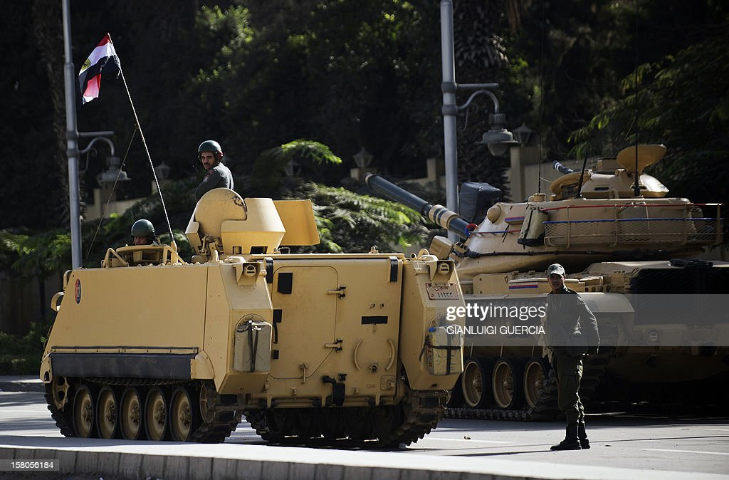 Egyptian soldiers sit on an armoured personnel carrier (APC) flying their national flag next to a tank deployed outside the presidential palace in Cairo on December 10, 2012. President Mohamed Morsi has ordered Egypt's army to 'cooperate' with police and given it powers of arrest until the results of a referendum to be held this weekend, according to a decree obtained by AFP. AFP PHOTO/GIANLUIGI GUERCIA