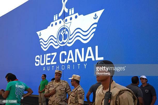 Egyptian soldiers stand beside a logo for the Suez Canal Authority near a section of the New Suez Canal operated by the Suez Canal Authority in...
