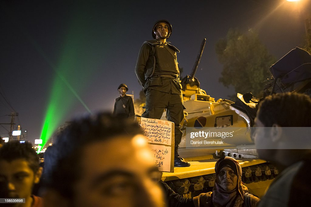 Egyptian soldiers stand guard as protestors opposing President Mohammed Morsi gather during a demonstration at the Presidential Palace on December 18, 2012 in Cairo, Egypt. Hundreds of people gathered in front of the Presidential Palace and in Tahrir Square to protest against President Mohammed Morsi and the alleged rigging of the first round of voting in the constitutional referendum.