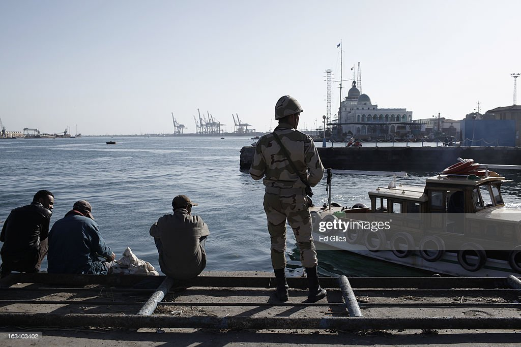 Egyptian soldiers stand guard at the Suez Canal as Port Said residents look on after the announcement of the final verdict in the case of the Port Said football massacre, on March 9, 2013, in Port Said, Egypt. Over seventy football fans of the Al Masry team were killed during a stadium brawl that took place after a match between the Al Masry and Al Ahly teams in the northern Egyptian city in February 2012. Two senior police officers, the Port Said Security Director Essam Samak and head of the Port Said Water Bodies Security Department, Mohammed Saad, received 15 year sentences, while seven other police officers were acquitted. Five Port Said citizens received life sentences on Saturday, and twenty one civilian death sentences handed down in a January ruling on the same case were confirmed. (Photo by Ed Giles/Getty Images).