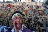 Egyptian soldiers stand guard behind barbed wire as protesters demonstrate outside the defence ministry the headquarters of the Supreme Council of...