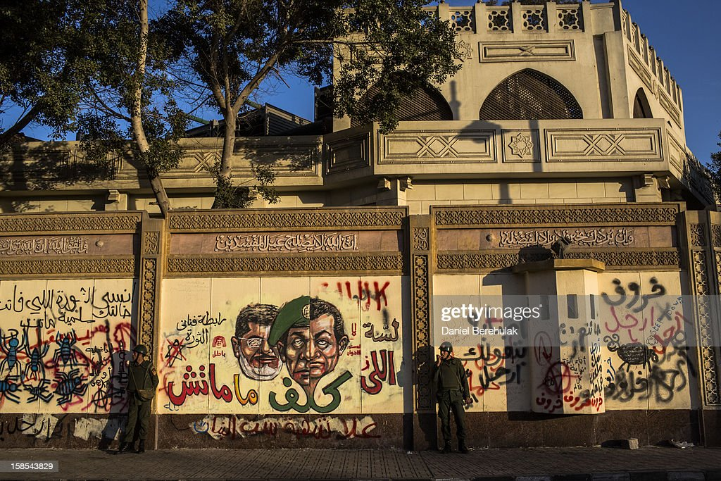 Egyptian soldiers stand guard in front of anti-SCAF graffiti on the walls of the Presidential Palace prior to the start of a demonstration opposing president Mohammed Morsi on December 18, 2012 in Cairo, Egypt. Hundreds of people gathered in front of the Presidential Palace and in Tahrir Square to protest against President Mohammed Morsi and the alleged rigging of the first round of voting in the constitutional referendum.
