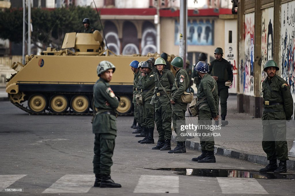 Egyptian soldiers stand guard near the presidential palace in Cairo on December 13, 2012. Egypt's crisis showed no sign of easing as the army delayed unity talks meant to ease political divisions and the opposition set near-impossible demands for taking part in a looming constitutional referendum.