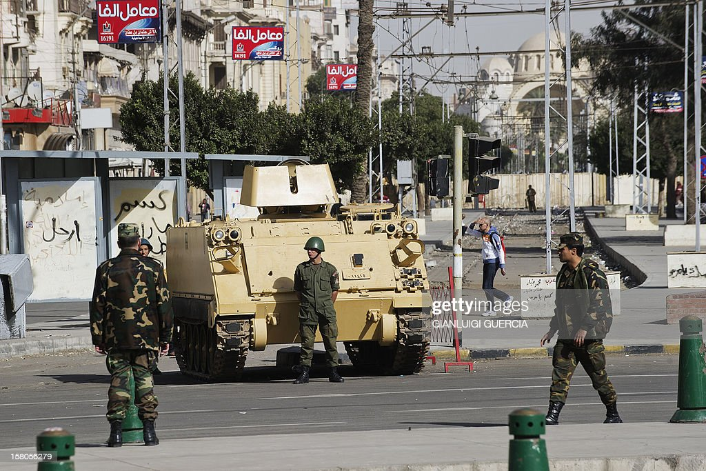 Egyptian soldiers stand guard next to an armoured personnel carrier (APC) deployed outside the presidential palace in Cairo on December 10, 2012. President Mohamed Morsi has ordered Egypt's army to 'cooperate' with police and given it powers of arrest until the results of a referendum to be held this weekend, according to a decree obtained by AFP. AFP PHOTO/GIANLUIGI GUERCIA