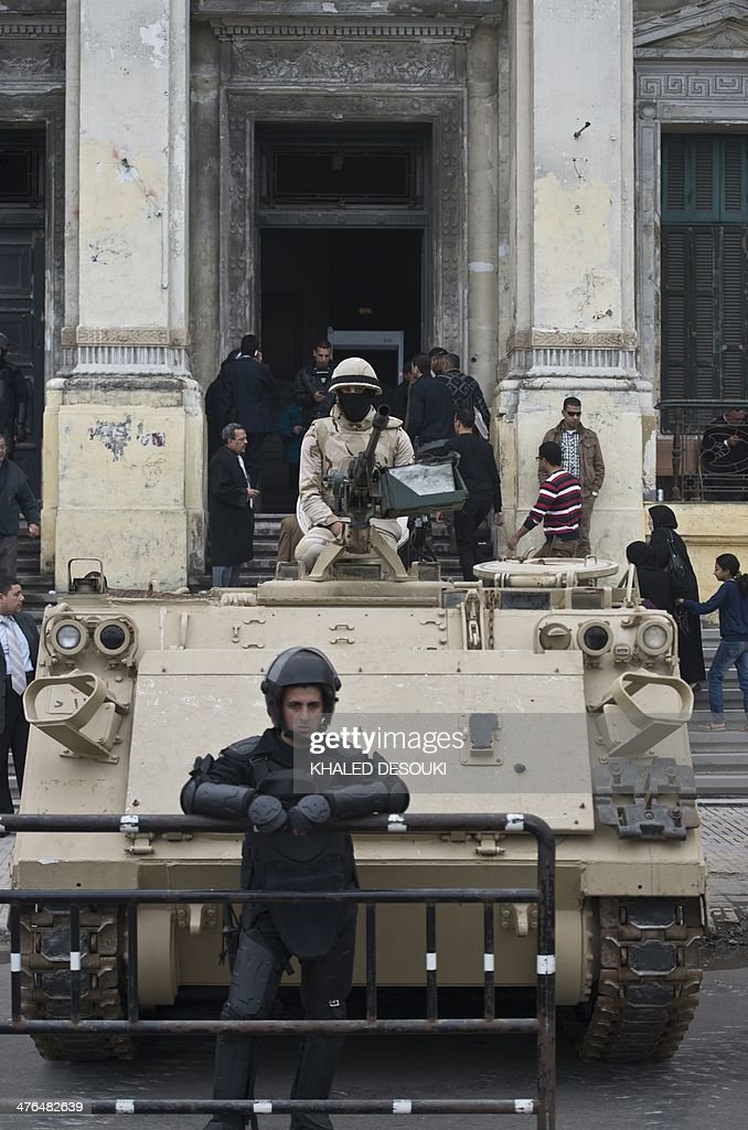 Egyptian soldiers stand guard on an armoured personnel carrier (APC) outside the criminal court in Egypt's Mediterranean city of Alexandria on March 3, 2014, during the retrial of the two policemen Awad Ismail Suleiman and Mahmoud Salah Mahoud, who are accused of using excessive force and killing 28-year-old blogger Khaled Said. The two policemen were sentenced to ten years in jail for the killing of the blogger whose death rallied protesters in the 2011 revolt that toppled Hosni Mubarak. AFP PHOTO/KHALED DESOUKI
