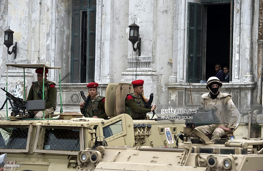 Egyptian soldiers stand guard on armoured personnel carriers (APC) outside the criminal court in Egypt's Mediterranean city of Alexandria on March 3, 2014, during the retrial of the two policemen Awad Ismail Suleiman and Mahmoud Salah Mahoud, who are accused of using excessive force and killing 28-year-old blogger Khaled Said. The two policemen were sentenced to ten years in jail for the killing of the blogger whose death rallied protesters in the 2011 revolt that toppled Hosni Mubarak.