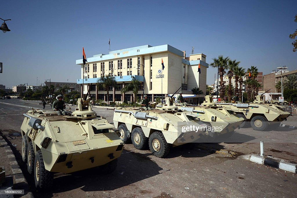 Egyptian soldiers stand guard on armoured vehicles outside the Suez governorate a day after clashes with riot police on January 26, 2013. At least seven people died in Friday's anti-government protests, according to the health ministry, six in Suez and one in Ismailiya, in the northeast, while 456 were injured in unrest across 12 provinces. AFP PHOTO / STR