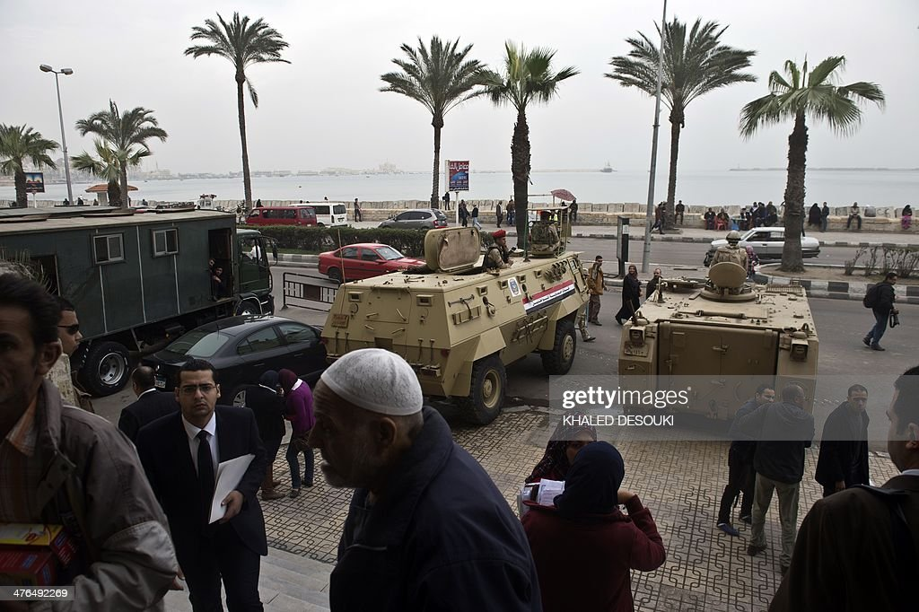 Egyptian soldiers stand guard with armoured personnel carriers (APC) outside the criminal court in Egypt's Mediterranean city of Alexandria on March 3, 2014, during the retrial of the two policemen Awad Ismail Suleiman and Mahmoud Salah Mahoud, who are accused of using excessive force and killing 28-year-old blogger Khaled Said. The two policemen were sentenced to ten years in jail for the killing of the blogger whose death rallied protesters in the 2011 revolt that toppled Hosni Mubarak.
