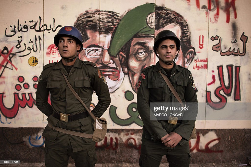 Egyptian soldiers stand in front of a graffiti on the walls of the Presidential Palace in Cairo on December 11, 2012. Protesters gathered in Cairo for rival rallies over a deeply disputed constitutional referendum proposed by Egypt's Islamist president, Mohamed Morsi, raising fears of street clashes . AFP PHOTO/MARCO LONGARI